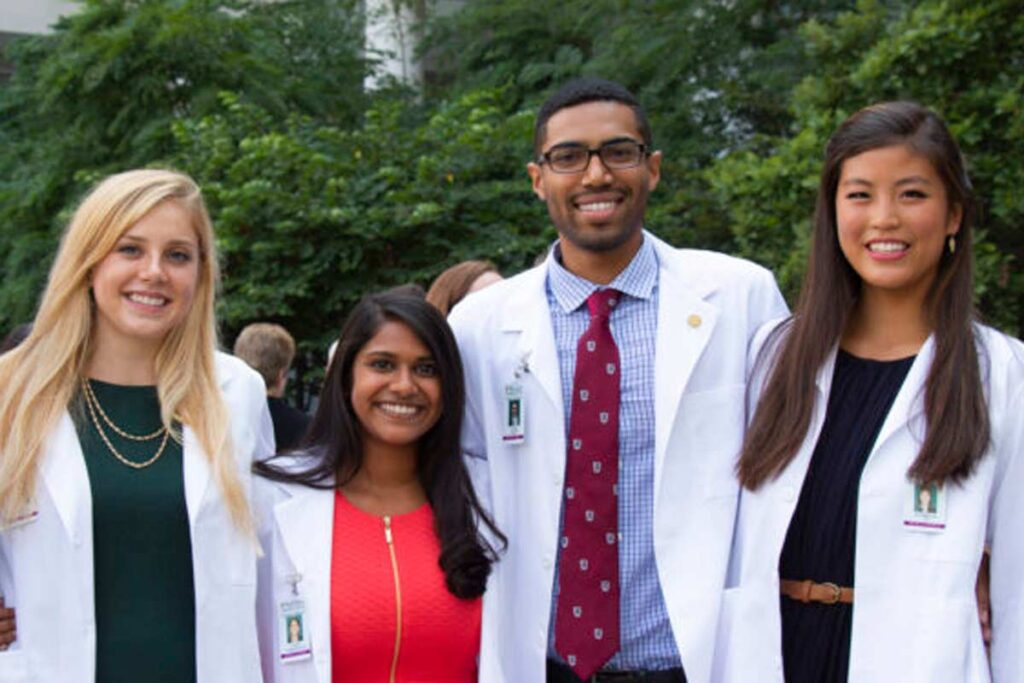 Incoming medical students pose for a smile after receiving their white coats