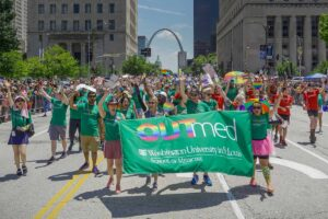Students, faculty and staff march behind at green banner that says OUTmed at parade during Pride St. Louis