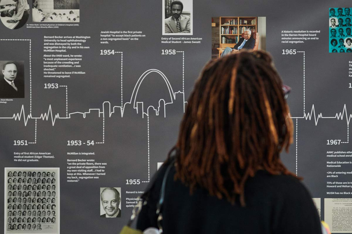 A Black woman views a timeline showing the history of desegregation on the medical campus