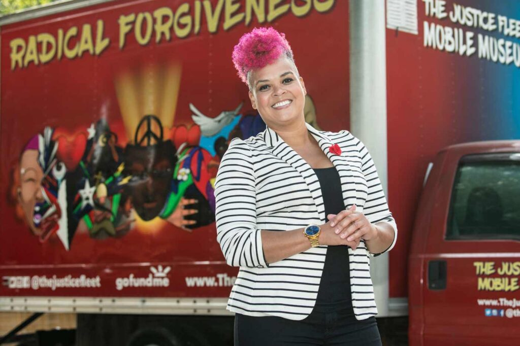 """Amber Johnson, PhD, stands in front of a red box truck. """"Justice Fleet Mobile Museum"""" and """"Radical Forgiveness"""" are painted on the truck."""