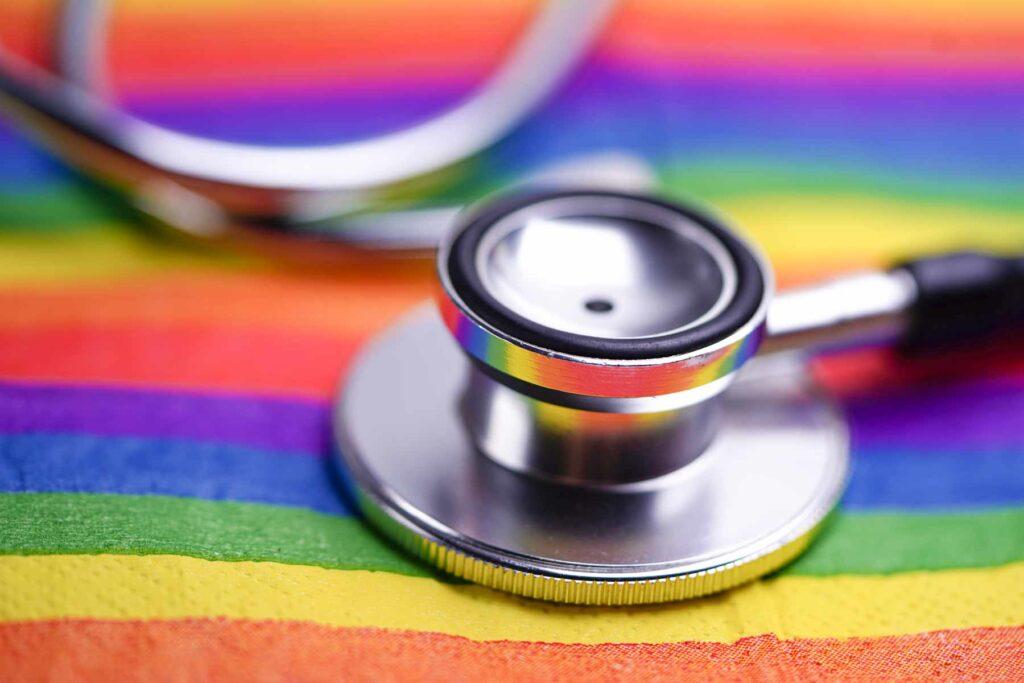 A stethoscope lies atop a rainbow flag