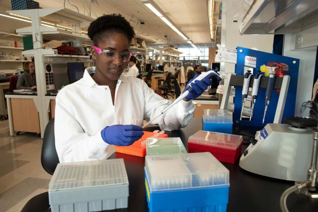 A Black woman in a basic science lab uses a pipette